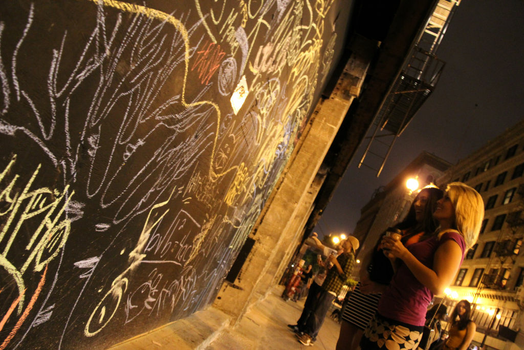 A downtown wall displays words of protest written in chalk.