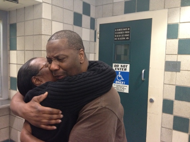 Wilma Register, Kash Delano Register and a former inmate Keith Chandler hug Friday afternoon. Chandler was instrumental in helping Register with his legal appeals.