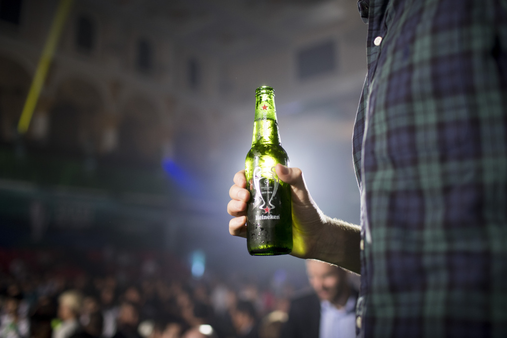 A man holds a bottle of beer during the UEFA Champions League Trophy Tour on April 3, 2017 in Phnom Penh, Cambodia.