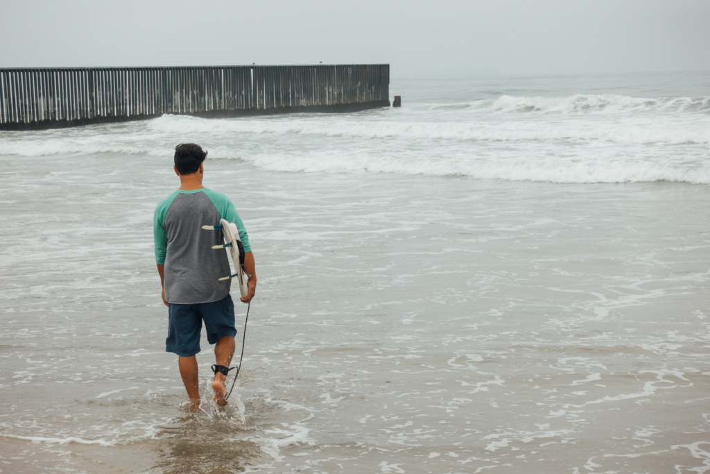 L.A. artist Diego Palacios heads out to surf at the border between the U.S. and Mexico on August 12th, 2017. The Beach at Border Field State Park in San Diego, CA is located in the farthest Southwest corner of the United States, separated from Playas de Tijuana by an 18-foot high fence.