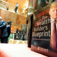 Real estate mogul Donald Trump (background) speaks as course material stands on display during a news conference announcing the establishment of Trump University May 23, 2005 in New York City.