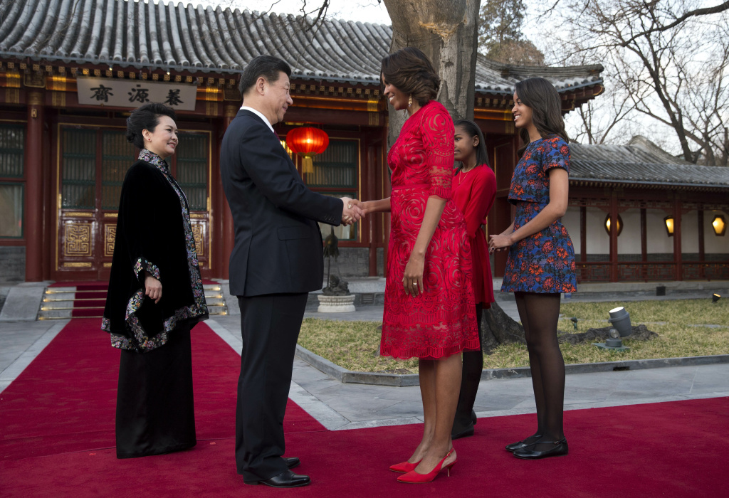 BEIJING, CHINA - MARCH 21: U.S. first lady Michelle Obama shakes hand with Chinese President Xi Jinping, as Michelle Obama's daughters Malia (R) and Sasha (2ndR) and Peng Liyuan, wife of Xi Jinping (L) look on before they proceed to a meeting at the Diaoyutai State guest house on March 21, 2014 in Beijing, China. Michelle Obama's one-week-long visit in China will be focused on educational and cultural exchanges. (Photo by Andy Wong-Pool/Getty Images)