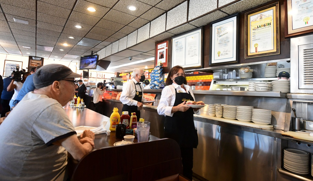 Customers sit at the counter awaiting their order at the reopening of Langer's Delicatessen-Restaurant in Los Angeles on June 15, 2021, as California re-opens, lifting its Covid-19 restrictions