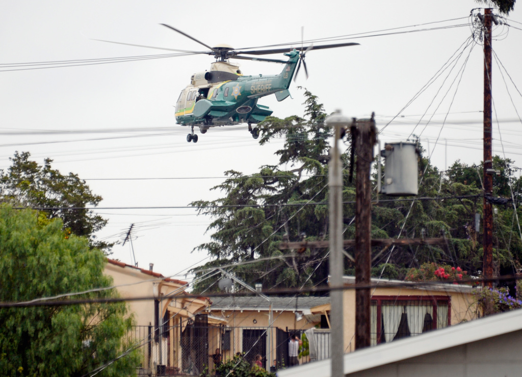 A Los Angeles County Sheriff's SWAT team  helicopter flies low over homes in the search zone during a massive manhunt for a suspect who attempted to kill two LAPD detectives on June 25, 2013 in Los Angeles, California.