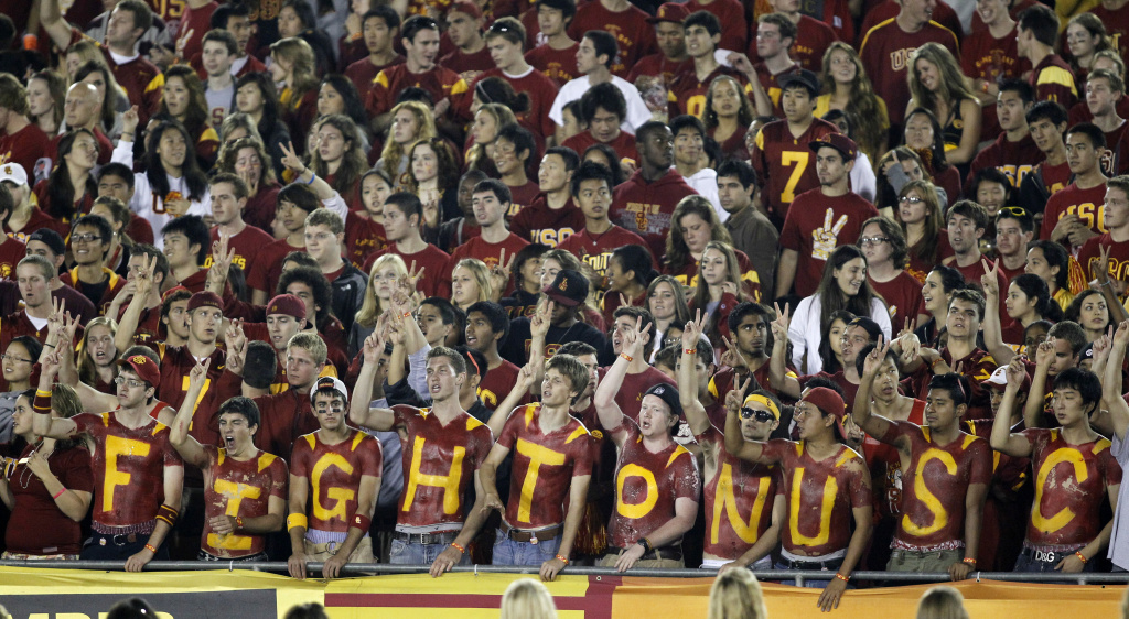 USC Fans cheer with their chests painted in the student section of the Los Angeles Memorial Coliseum during an NCAA college football game.