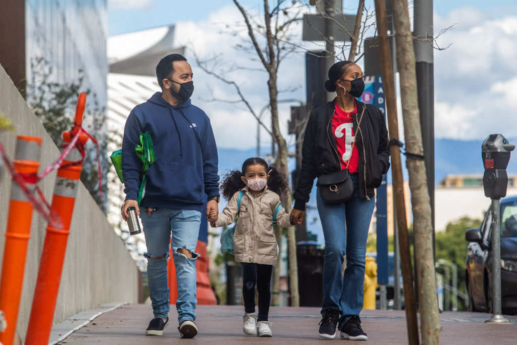 A family walks wearing masks in Downtown Los Angeles on March 22, 2020, during the coronavirus (COVID-19) outbreak. - The US president on March 22 said he had ordered the deployment of emergency medical stations with capacity of 4,000 hospital beds to coronavirus hotspots around the United States. (Photo by Apu GOMES / AFP) (Photo by APU GOMES/AFP via Getty Images)