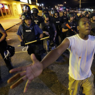 Protesters walk in front of a line of police as authorities try to disperse a demonstration in Ferguson, Mo. early Wednesday. The St. Louis suburb saw less violence than recent nights of protests.
