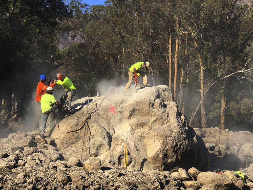 In this photo provided by the Santa Barbara County Fire Department, demolition workers break down boulders Sunday, Jan. 14, 2018, that are scattered throughout Montecito following the deadly mudslides containing rocks and debris that struck the area following heavy rains on Tuesday, Jan. 9.