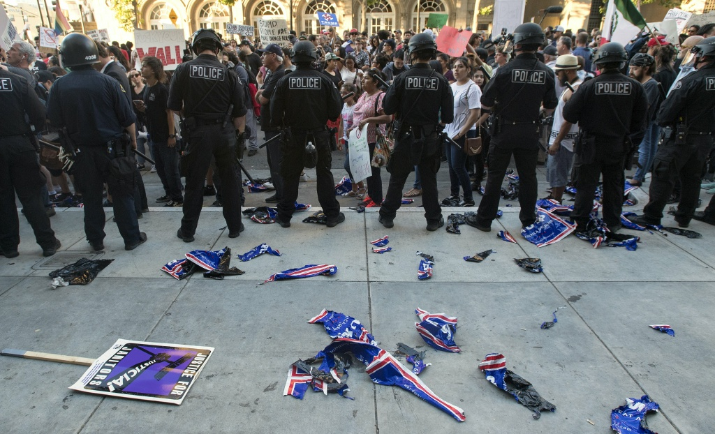 Torn Trump signs are seen on the ground behind a police skirmish line during a protest near where Republican presidential candidate Donald Trump held a rally in San Jose, California on June 2, 2016.