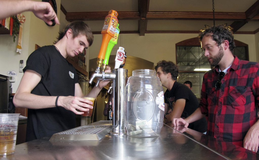 In this Oct. 3, 2013 photo, Dylan Maz pours beer during a tour on Thursday, Oct. 3, 2013 at Lakefront Brewery in Milwaukee. The federal government shutdown could leave America's craft brewers with a serious hangover.