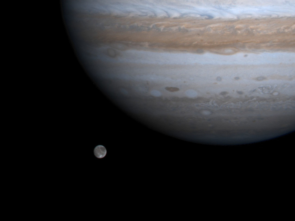 The solar system's largest moon, Ganymede, is pictured with Jupiter in a photo by NASA's Cassini spacecraft, Dec. 3, 2000. NASA's Juno mission will get close to Ganymede on Monday.