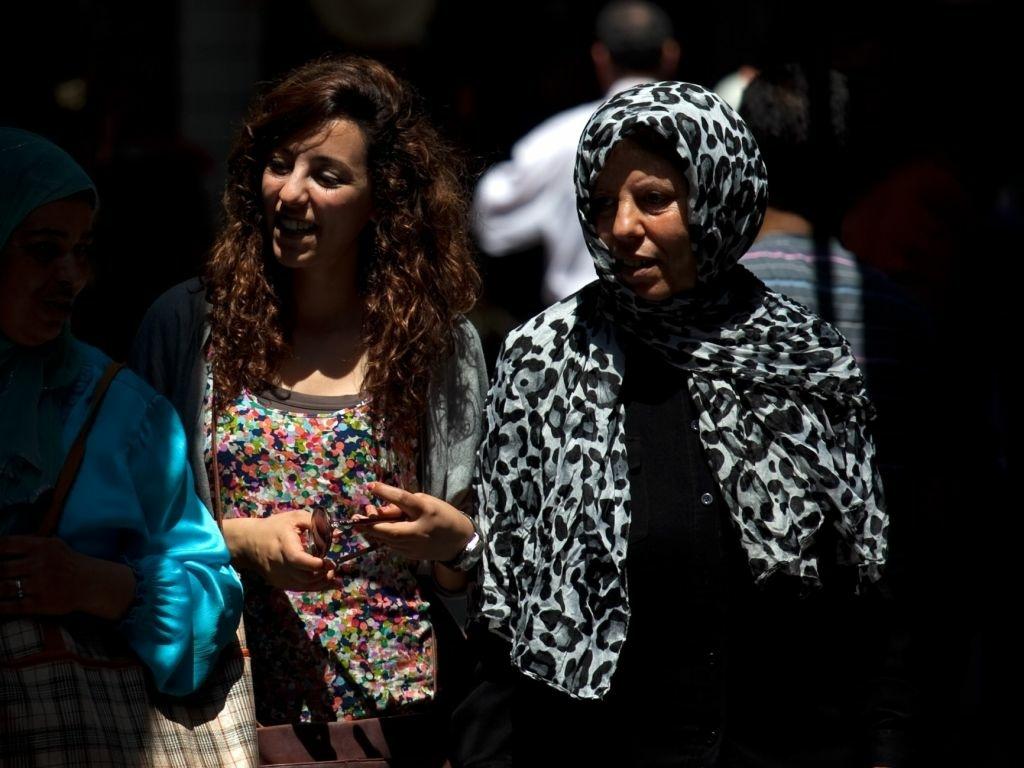 Tunisian women walk through the narrow streets of Tunis' medina, or marketplace.