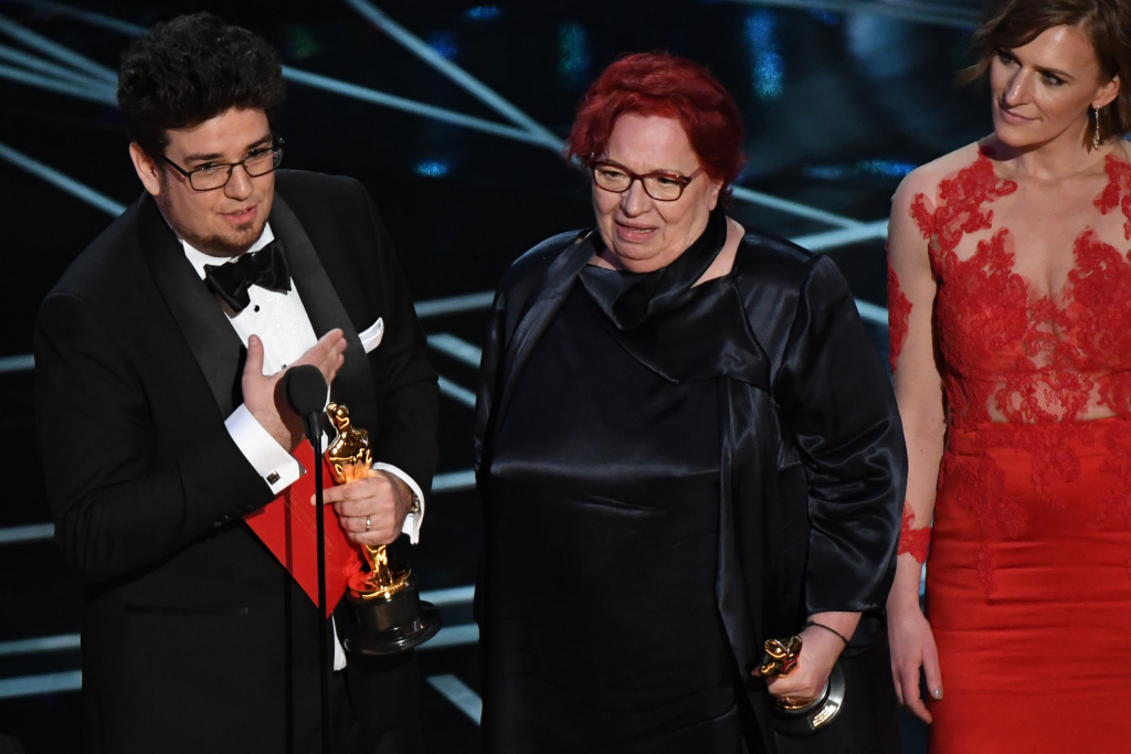hungarian editor Kristof Deak (L) and producer Anna Udvardy (C) deliver a speech on stage after they won the Best Short Film (Live Action) award for