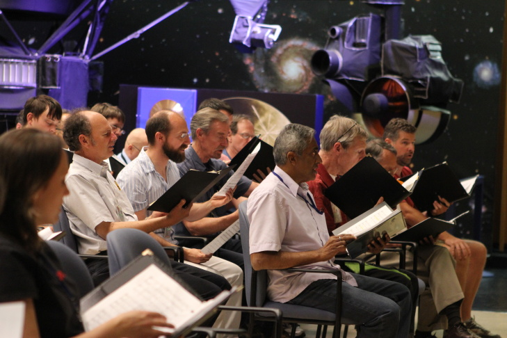 Members of the choir at NASA's Jet Propulsion Laboratory rehearse in the Von Karmen auditorium on the JPL campus, which displays models of the robotic technology JPL has sent into space.