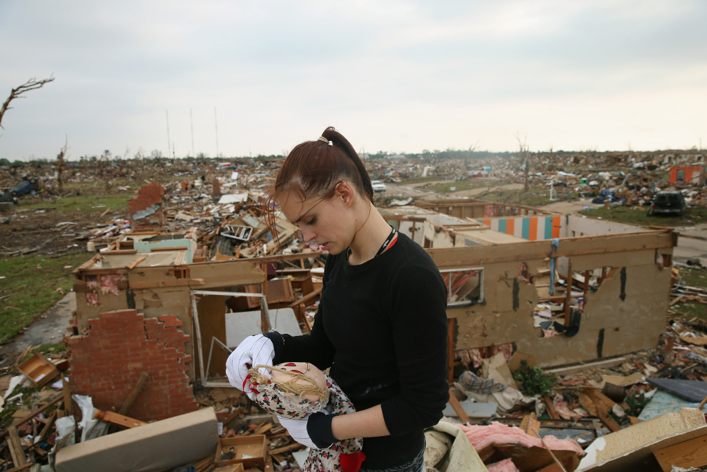 Sabrina Mitchell recovers a stuffed doll as she searches for belongings in what was the second floor bedroom of her home which was destroyed by a tornado on May 24, 2013 in Moore, Oklahoma. A two-mile wide EF5 tornado touched down in Moore May 20 killing at least 24 people and leaving behind extensive damage to homes and businesses. U.S. President Barack Obama promised federal aid to supplement state and local recovery efforts.