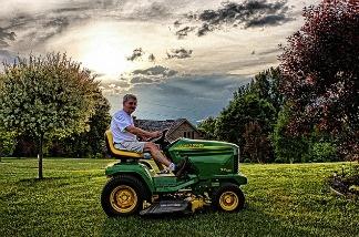 A man sits atop a lawn mower.