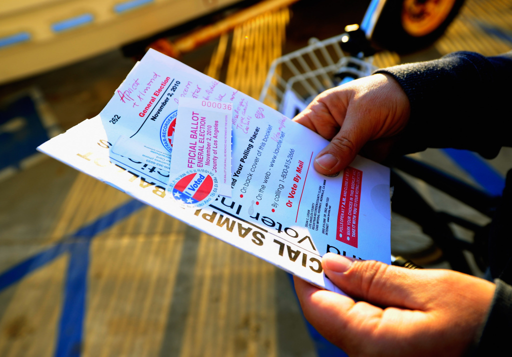 File: A voter holds a sample ballot with her grocery list scribbled on the front page after voting in the midterm elections in 2010.