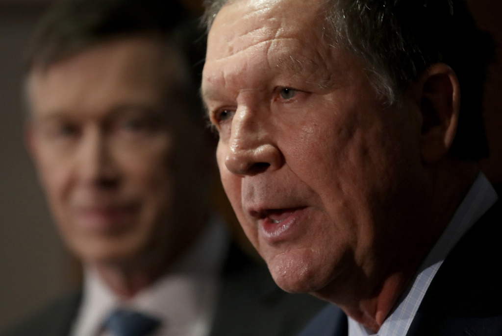 Gov. John Kasich (R) (R-OH) speaks as Gov. John Hickenlooper (L) (D-CO) listens during a press conference February 23, 2018 in Washington, DC.