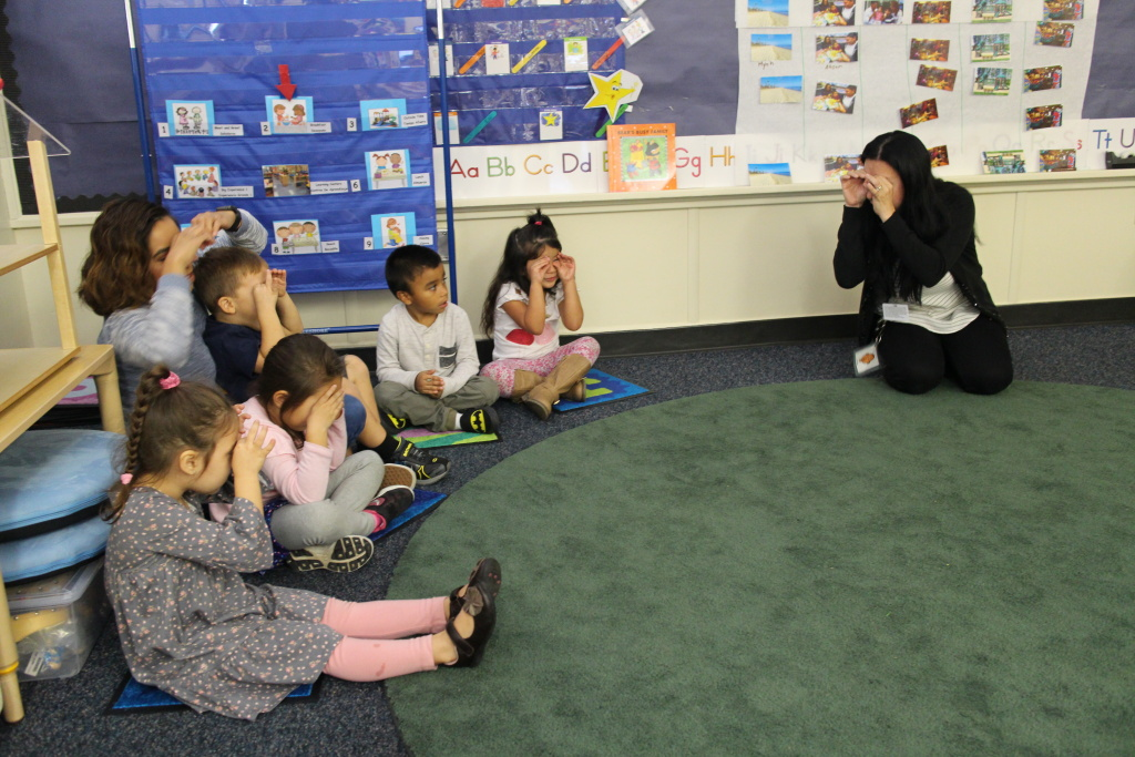 Teacher Cathy Barraza sings a song and acts out the motions with preschoolers at Educare Los Angeles, Long Beach.