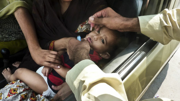 A child is inoculated with the polio vaccine at a traffic checkpoint just outside Pakistan's capital, Islamabad. Roadside vaccinations help health workers reach children in mobile populations.