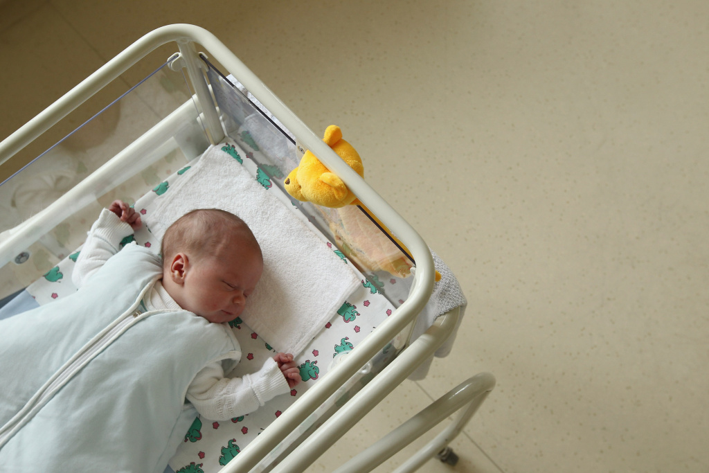 A 4-day-old newborn baby lies in a baby bed in the maternity ward of a hospital on August 12, 2011.