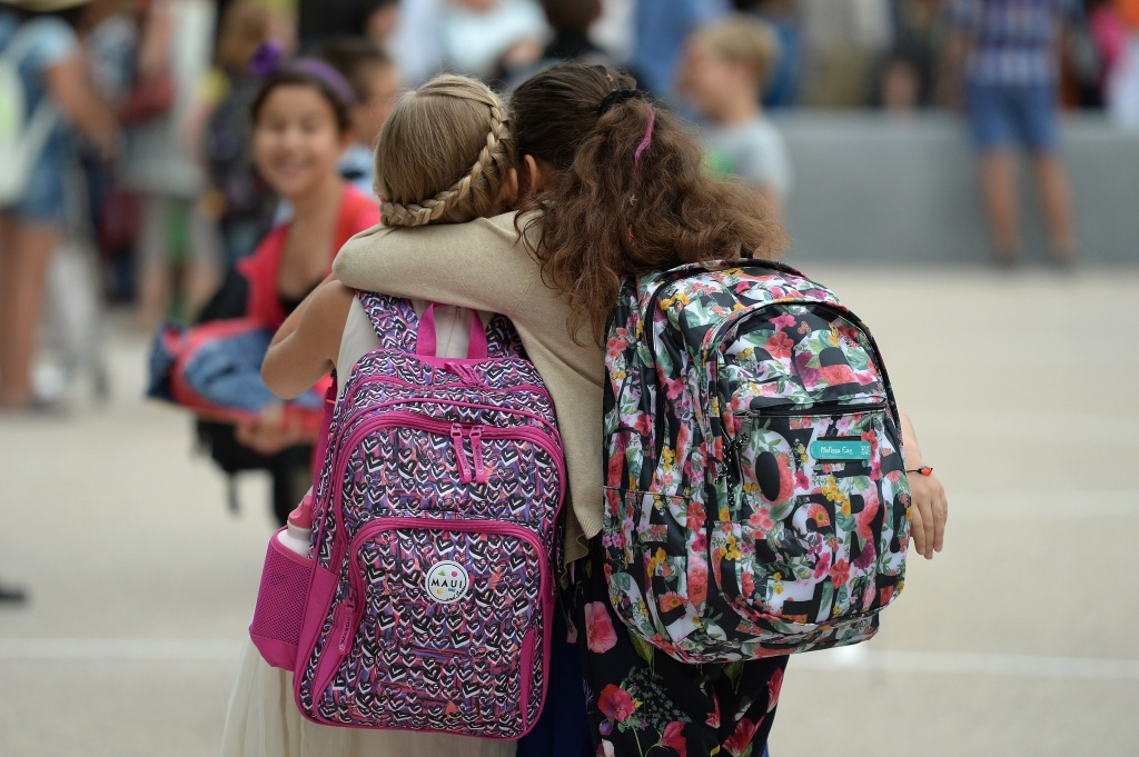 Girls hug each other outside the European school of Strasbourg in France.