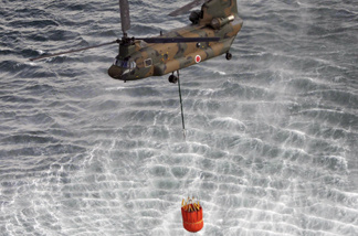 This aerial shot shows a Japanese Self Defence Force's CH-47 Chinook helicopter holding more than seven tonnes water each with large buckets from the sea near Natori in Miyagi prefecture on March 17, 2011.