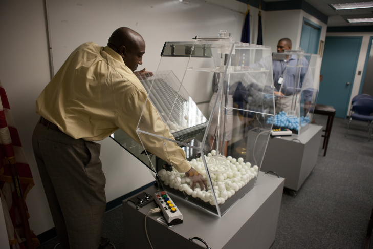 Cristine Nguyen (L) and Vince McClure (R) do final checks one one of the Selective Service Systems two draft lottery machines prior to their monthly test.
