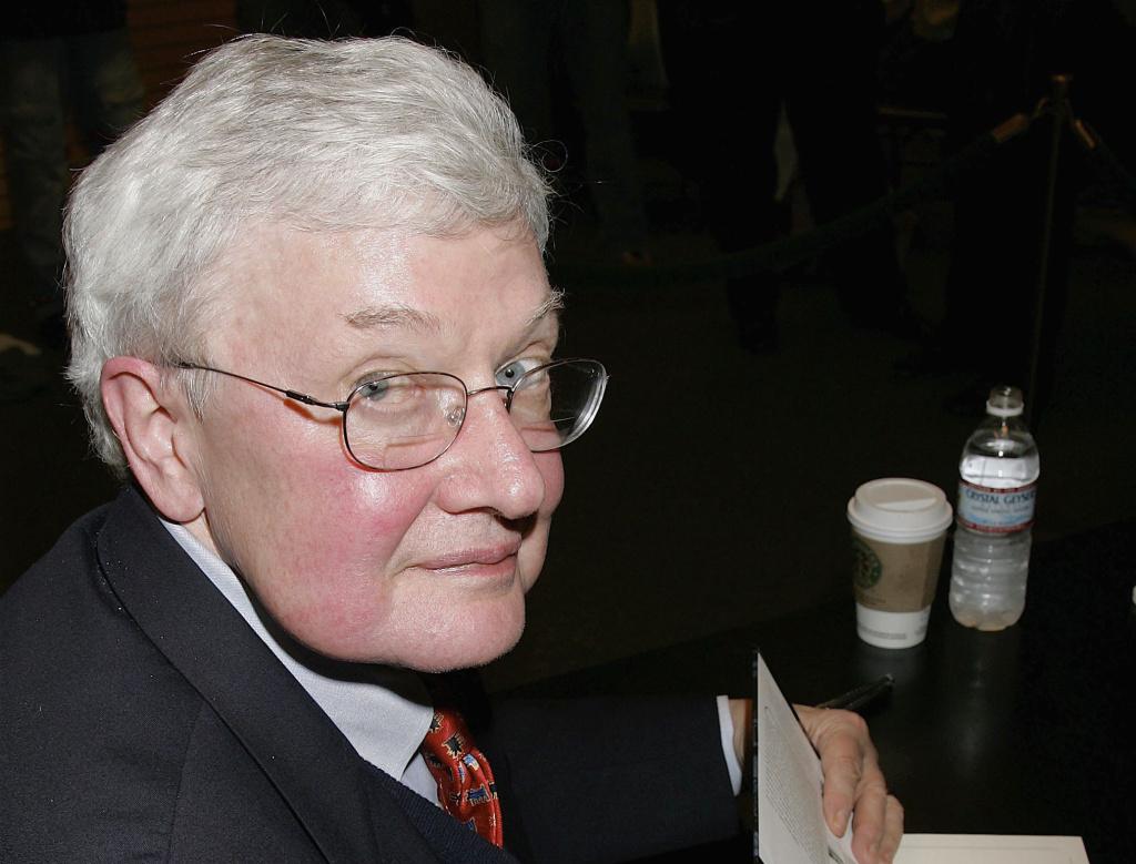 Film critic Roger Ebert signs his new book