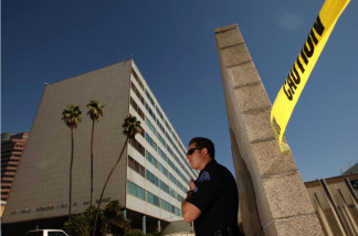 A Los Angeles police officer stands guard outside Parker Center headquarters for the Los Angeles Police Department (LAPD), as a suspicious package is removed from the street in front of the 911 Metro Dispatch Center on October 8, 2008 in Los Angeles, California.