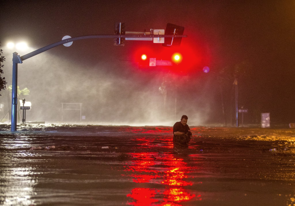 Lanny Dean, from Tulsa, Oklahoma, wades through water on flooded Beach Blvd. in Biloxi, Mississippi as the eye of Hurricane Nate pushes ashore on Sunday, October 8, 2017.