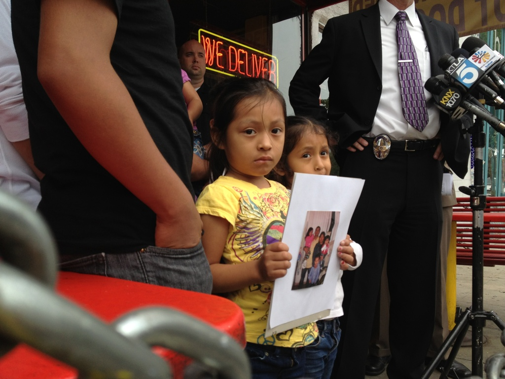 Raul Lopez's daughter, Celeste, 6, holds up a family photo at a news conference announcing the $50,000 reward for information leading to the arrest and conviction of the suspect who shot and killed Lopez.