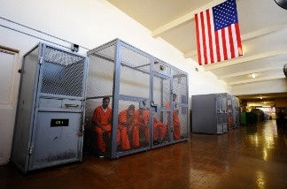 Inmates at Chino State Prison sit inside a metal cage in the hallway on December 10, 2010 in Chino, California.