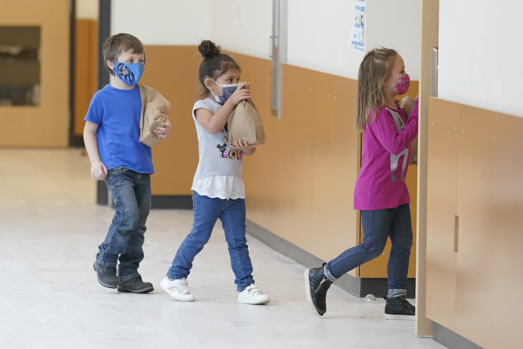 Students carry sack lunches at Elk Ridge Elementary School in Buckley, Wash. On Monday, USDA unveiled a new program that would feed millions of children over the summer, when many schools are closed.