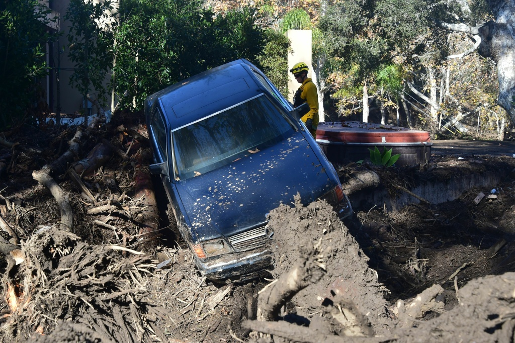 A firefighter stands near a car caught up in a mud slide in Montecito, California on January 12, 2018.