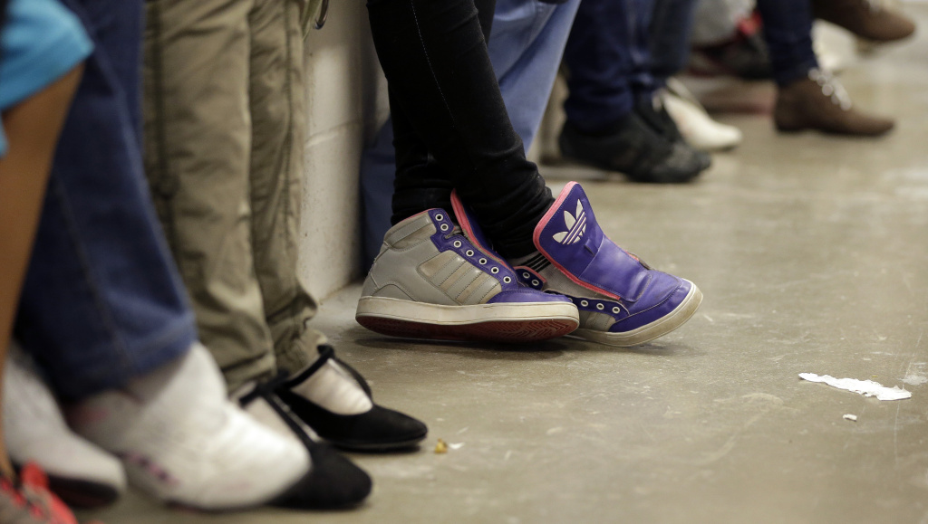 File: Detainees, with the shoe strings removed, wait at a U.S. Customs and Border Protection processing facility, on June 18, 2014, in Brownsville, Texas.