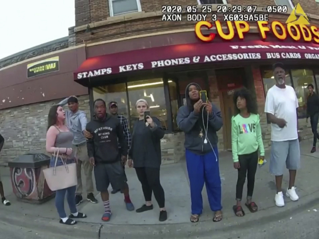 This image from a police body camera shows bystanders including Darnella Frazier (third from right) as Derek Chauvin, who was a police officer at the time, pressed his knee on George Floyd's neck in Minneapolis.