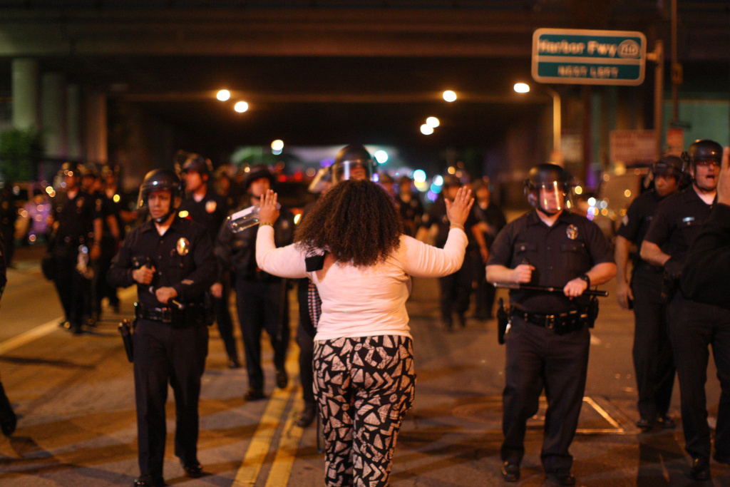 A woman faces police officers advancing to arrest anyone who fails to disperse as demonstrators react to the grand jury decision not to indict a white police officer who had shot dead an unarmed black teenager in Ferguson, Missouri, in the early morning hours of November 25, 2014 in Los Angeles.