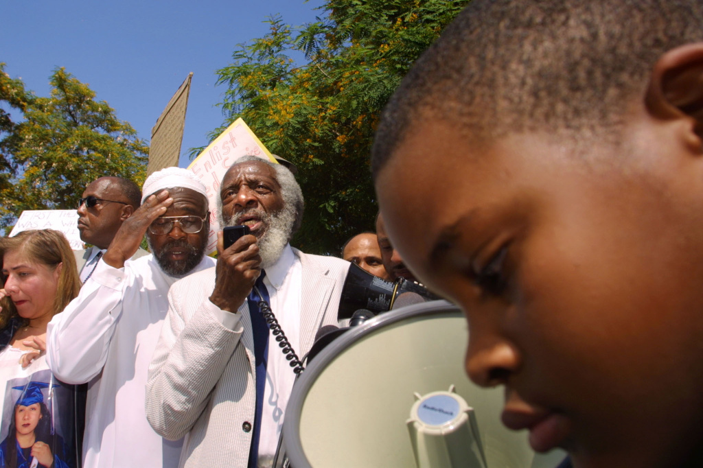 Civil rights activist Dick Gregory addresses protestors on July 12, 2002 in Inglewood, California. Demonstrators were calling for action against police in a videotaped incident in which a police officer is shown apparently smashing 16-year-old Donovan Jackson's head into a car, then striking him in the face.