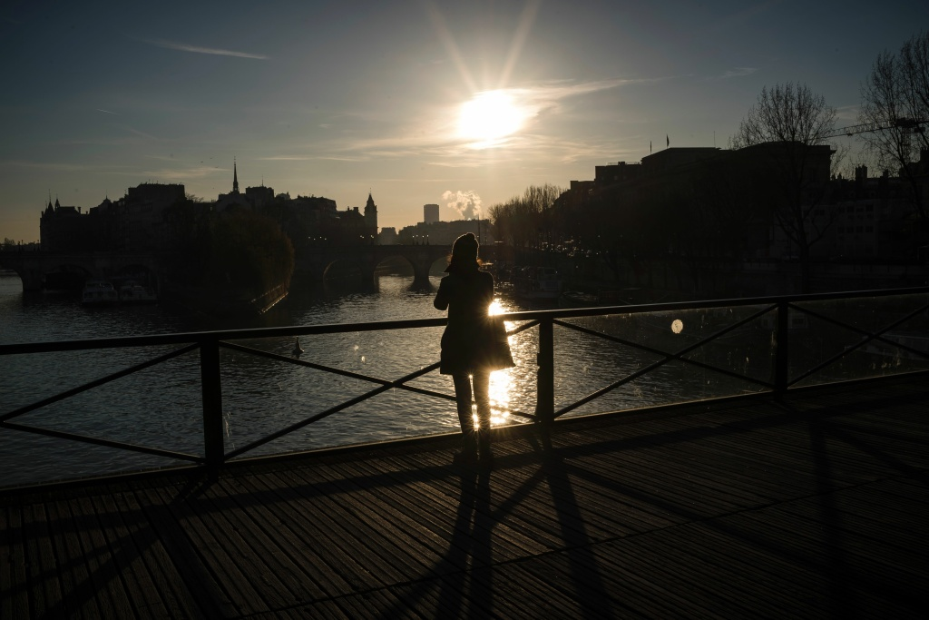 A woman takes a picture from the Pont des Arts bridge at sunrise, on January 6, 2017 in Paris.