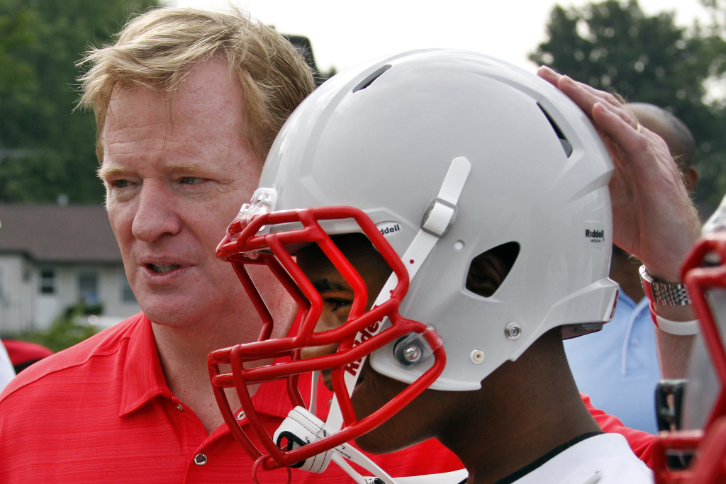 NFL commissioner Roger Goodell, left, poses with Jaqueal Hitchcock, 14, from the Akron Parents Pee Wee Football League in Akron, Ohio,  Saturday, Aug. 4, 2012. These youth football players from low income families are among thousands nationwide who benefit from a youth safety and helmet replacement program, partially sponsored by the NFL. Still, a new report finds that even after a decade of increasing awareness of the seriousness of concussions, young athletes still face a
