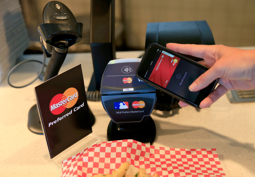 A fan uses MasterCard with Apple Pay to pay for garlic fries in this October 24, 2014 file photo taken in San Francisco, California. Many people who are eligible for federal health insurance subsidies don't have bank accounts, which makes it hard to pay premiums. By scanning a bar code sent to their smartphones instead, customers can pay with cash at convenience stores under a system in California.