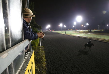 A track worker watches a horse run along the backstretch during morning workouts at Betfair Hollywood Park on December 21, 2013 in Inglewood, California.