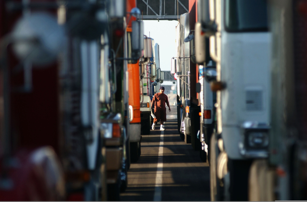 In this file photo, a trucker walks between rows of trucks lined up in anticipation of the re-opening of the Port of Los Angeles following a dock worker strike in 2002 in Los Angeles, California. On Thursday, November 20, 2014, truckers who had been on strike at the ports of Los Angeles and Long Beach reached an agreement to return to work.