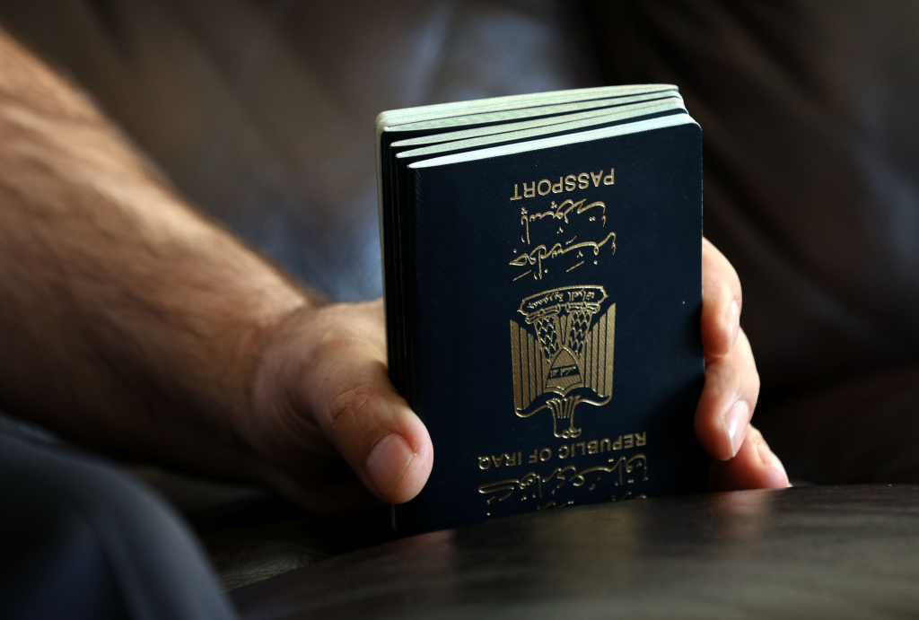 Fuad Sharef Suleman holds the passport of his family members in Arbil, the capital of the Kurdish autonomous region in northern Iraq, on January 30, 2017 after returning to Iraq from Egypt, where him and his family were prevented from boarding a plane to the US following US President Donald Trump's decision to temporarily bar travellers from seven countries, including Iraq.