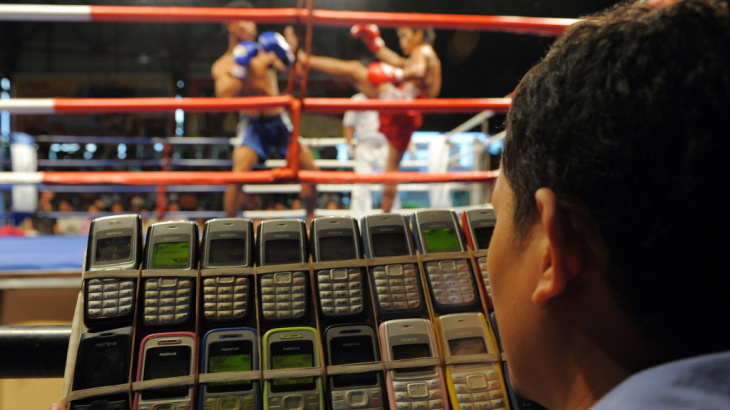 A Cambodian gambler talks on 18 cellphones at once at a boxing match in Phnom Penh in 2010. There are nearly 132 cellphones for every 100 Cambodians, but the country has also seen a surge in the number of landlines.