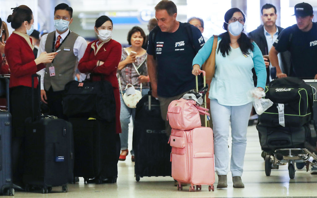 Members of a flight crew from Cathay Pacific Airways, wearing protective masks, stand in the international terminal after arriving on a flight from Hong Kong at Los Angeles International Airport (LAX) on February 28, 2020 in Los Angeles, California.