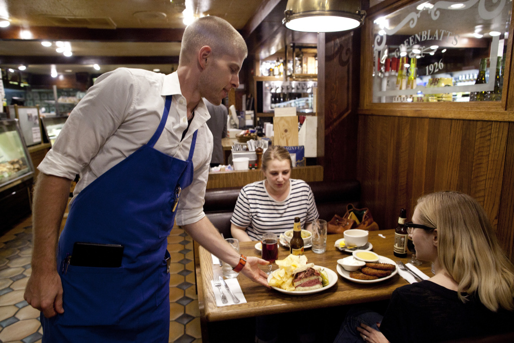 Chris Walsh serves a famous pastrami sandwich to Julia Batavia and Alison Govelitz at Greenblatt's in Hollywood. The proposed minimum wage increase in Los Angeles would adversely affect the business, considering the deli is open until 2 a.m. every day and the food takes a lot of time to prepare, owner Jeff Kavin said.
