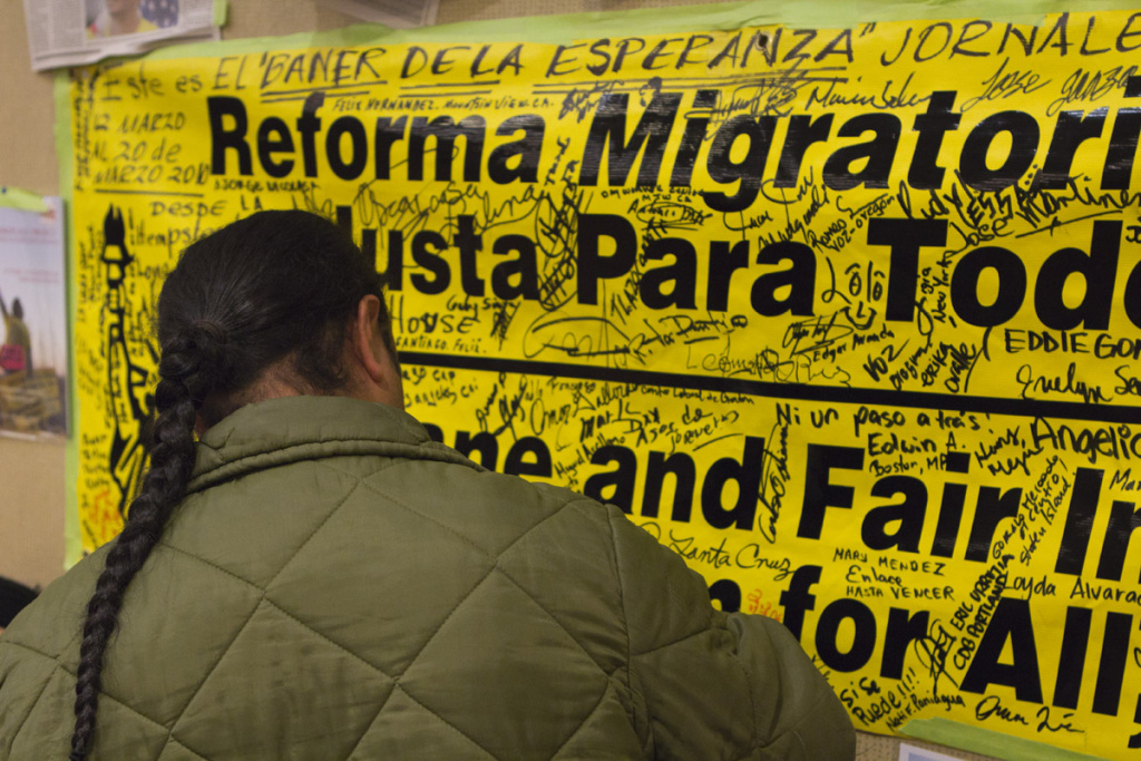A rally attendee signs a banner in support of immigration reform.