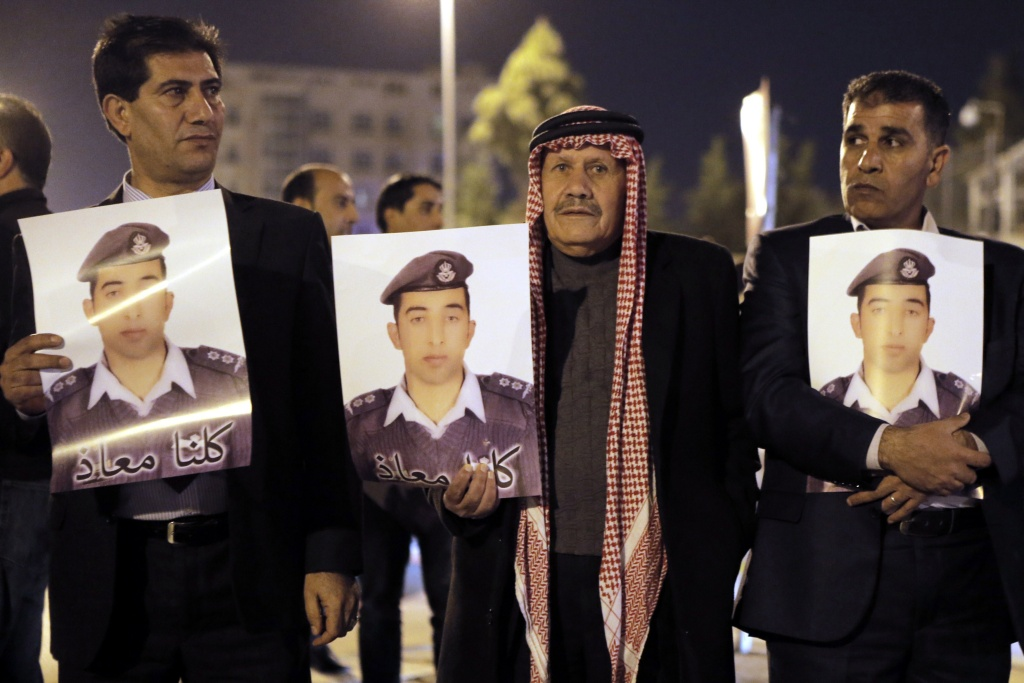 File: Relatives of Jordanian air force pilot Maaz al-Kassasbeh, who crashed in Syria with a F-16 last month, carry posters with his portrait and a slogan reading in Arabic,